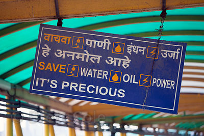A government sign encouraging citizens to conserve water, oil, and power, hanging in the Bandra Skywalk, Mumbai, India.