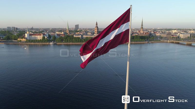 Aerial drone rising shot revealing Riga Old Town behind a large flag of Latvia