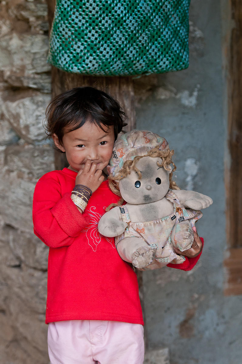 A kid shows off her bestest playmate, her doll. This photograph was shot in a small village in Bhutan.