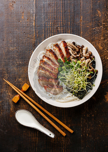 Rice noodles bowl with Peking Duck and mushrooms on wooden background