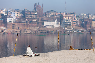 A man in white meditates on the banks of the Ganges River, Varanasi, India.