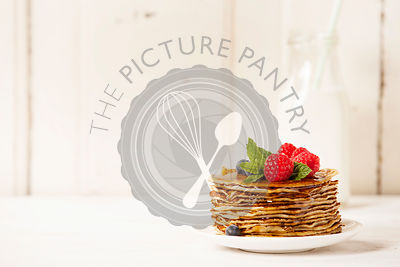 Milk and Stack of pancakes topped with berries and honey