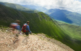 A female hiker and their dog descending from Grasmoor down Lad Hows above Buttermere on a sunny day in the English Lake Distr...