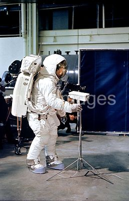 (April 1969) --- Astronaut Neil A. Armstrong, wearing an Extravehicular Mobility Unit (EMU), deploys a lunar surface televisi...