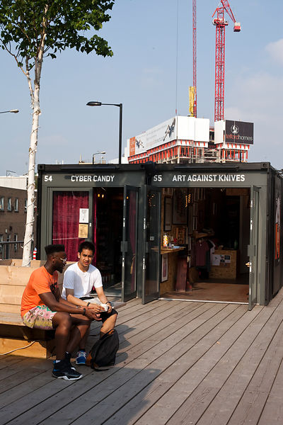 UK - London - Two fashionable young men sit and talk on the roof of the Boxpark - a so-called 'pop up mall' comprising of old shipping containers