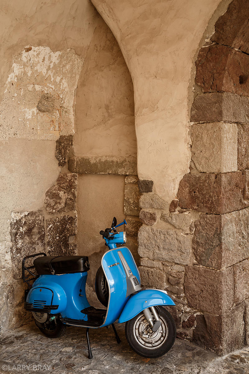 Blue Vespa scooter by archway in Lipari, Italy