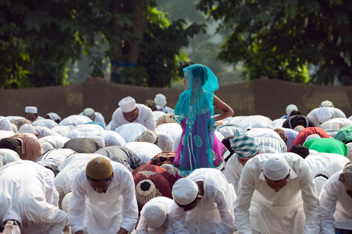 A girl in a blue headscarf stands over a group of Muslims praying during Eid al-Adha on Red Road in Kolkata, India. Eid al-Ad...