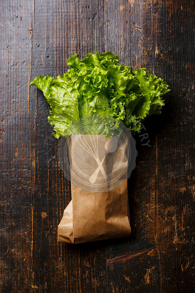 Fresh Green salad lettuce in paper bag on wooden background