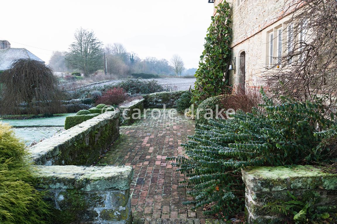 Brick terrace at the front of the Elizabethan house is framed with strong foliage plants including hypericum, variegated euon...