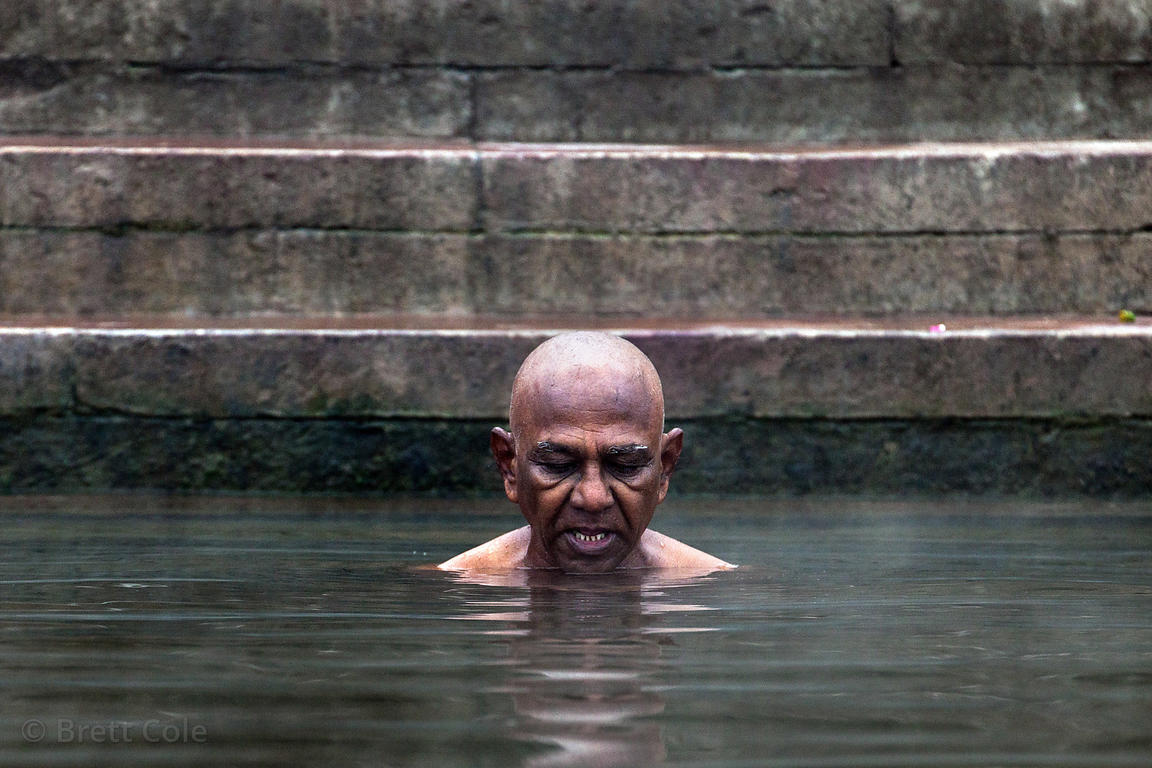 A man prays and bathes in the Ganges River, Varanasi, India.