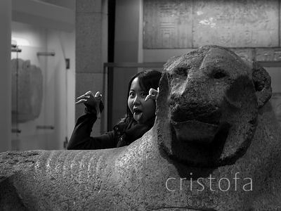 a girl poses by a lion in the British Museum