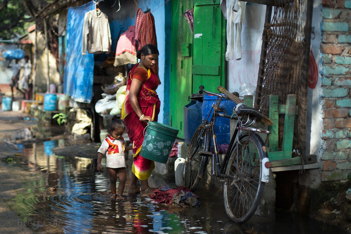 "A mother collects water in a bucket in a ""slum"" area in Salkia, Howrah, India"