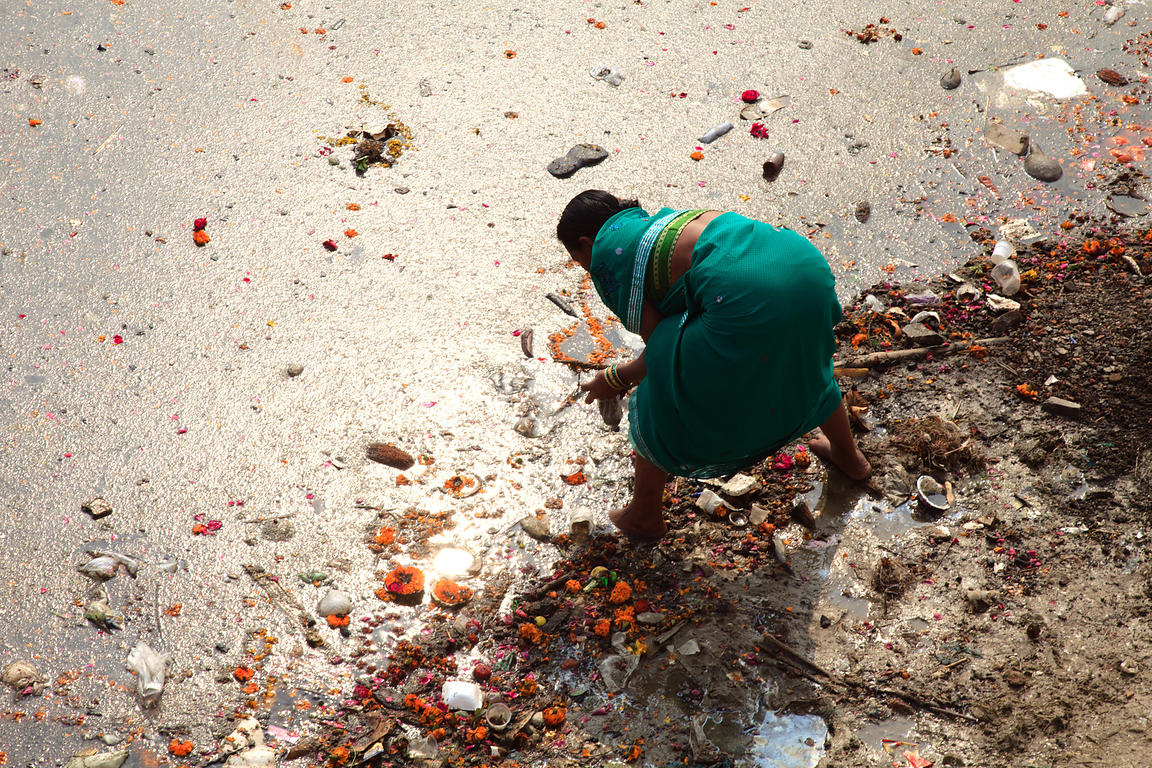 A woman works in dirty water on the Ganges River, Varanasi, India.