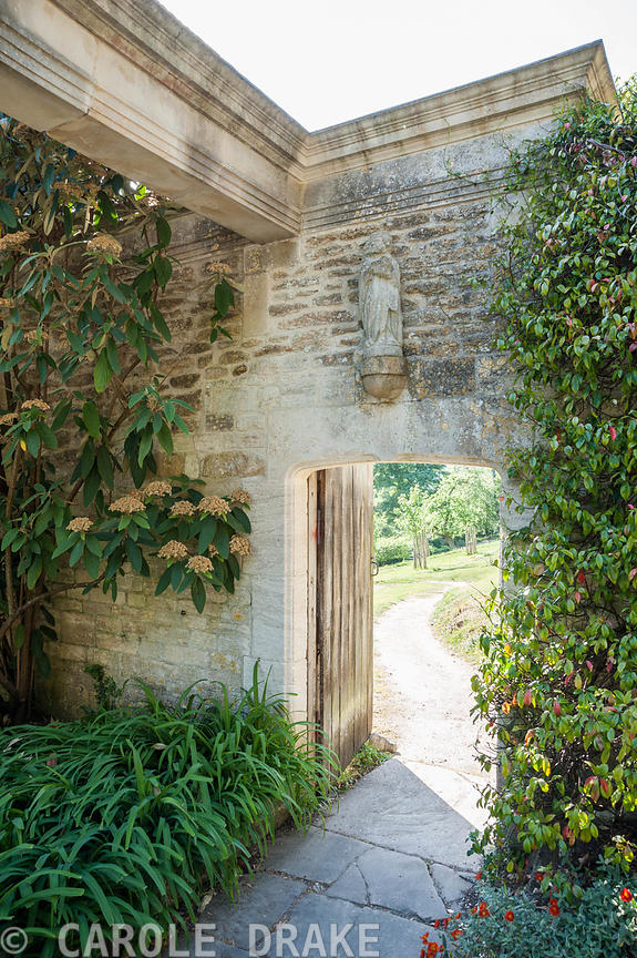Doorway from garden out into the adjoining orchard. Iford Manor, Bradford-on-Avon, Wiltshire