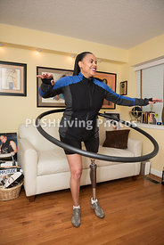 Woman with a prosthetic leg exercising with a Hula Hoop