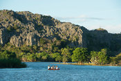 Tourist boat on a lake in front of Tsingy of the Ankarana massif, Madagascar