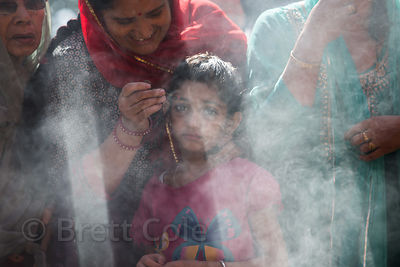 A mother applies mascara to her daughter as they pray during the Dussehra festival in Kullu, India
