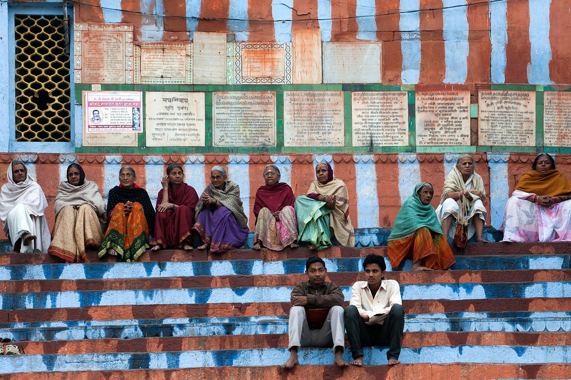 Elderly women sit on the striped steps of Kedar Ghat, Varanasi, India.