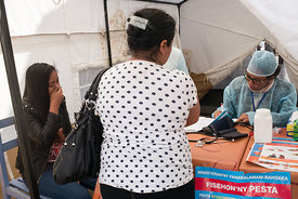 "A young woman (L) gestures as she is examined by a doctors at a healthcare checkpoint at the ""taxi-brousse"" station of Ampasa..."