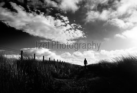 A black and white image of a hiker exploring the English Countryside, Muggleswick Common near Edmundbyers, England UK.