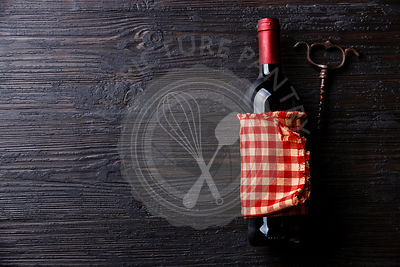 Wine bottle and corkscrew on Black Burned wooden background copy space