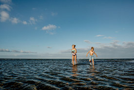 Nordic girl and boy running in the watter