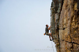 A male rock climber high on a steep vertical cliff.