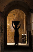 woman carrying water into her house, Goree Island, Senegal