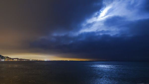 Wide Shot: Intensely Blue Moonlight Cutting A Thick Marine Layer Over Malibu's Waters