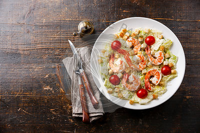 Caesar salad with shrimp and crouton on wooden background copy space