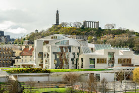 Scottish Parliament buiilding with Calton Hill in the background in Edinburgh.