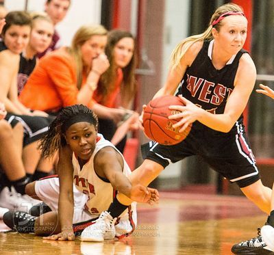 Iowa City High's Kiera Washpun (4) reaches to steal the ball from Waterloo West's Sammie Sproul (11) during the second half o...