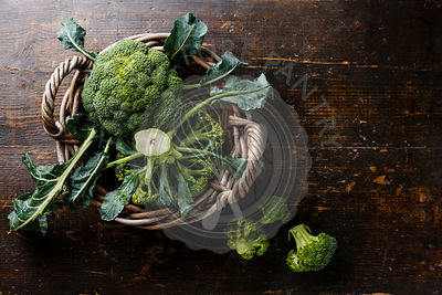 Raw broccoli in basket on wooden table background copy space