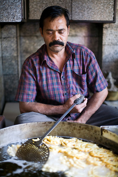 India - Delhi - A man squeezes batter from a cloth to make jalebis at the Old and Famous Jalebi Wala (at the corner of Dariba Khan and Chandni Chowk). Delhi, India