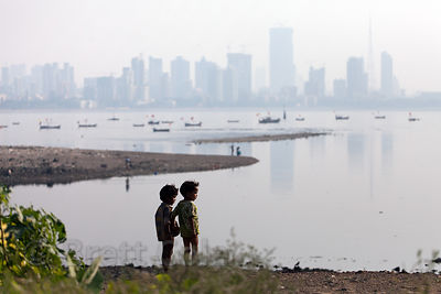Silhouette of two boys in front of Mahim Bay, Mumbai, India.