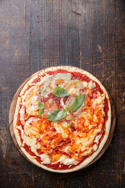 Pizza Margarita with basil leaves on wooden table