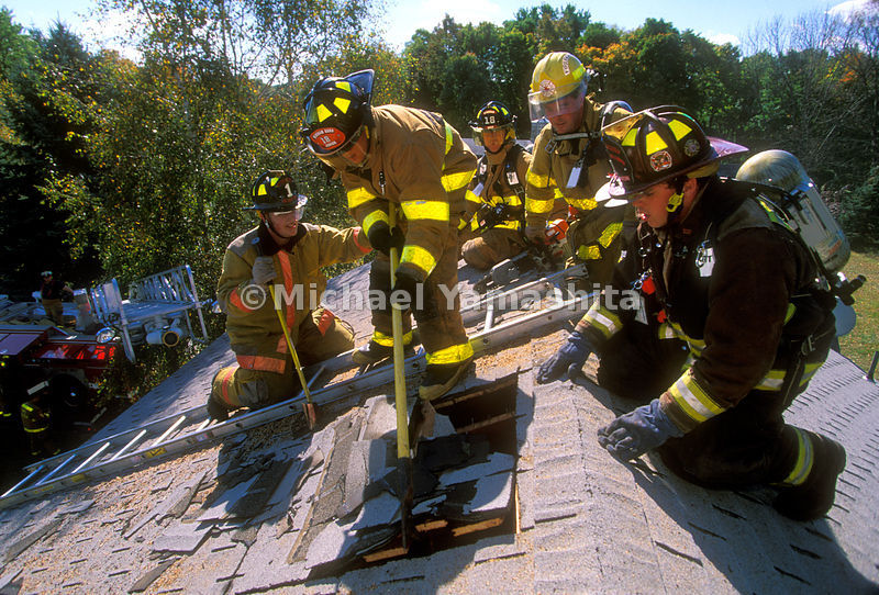 fire fighters breaking the roof of a house.