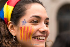 A protestor with the secession flag painted on her cheek for the protests for Catalonia independence at La Rambla in Barcelona, Spain