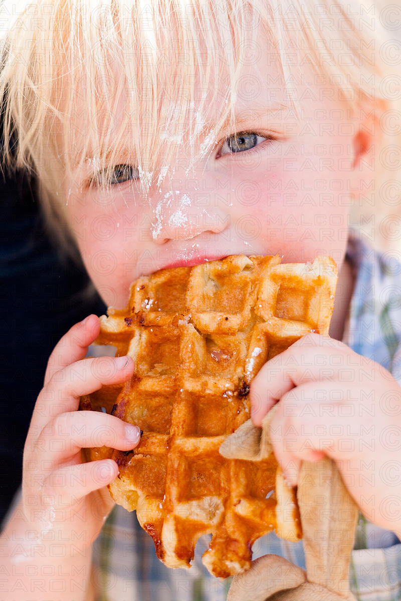 blond haired boy eating waffle