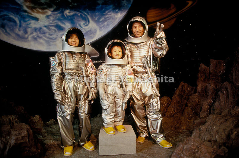 A successful lunar landing pleases a father and his children posing for a snapshot at Space World in Kitakyushu. The theme pa...