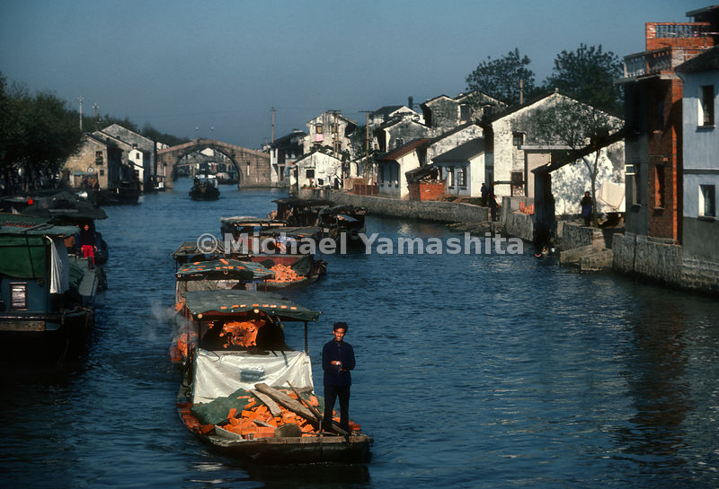 A line of boats transports bricks on the Grand Canal.