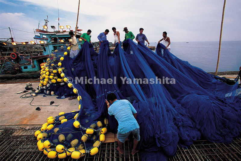 Fisherman sort their nets in Belwan, a Sumatran port on the Strait of Malacca, Indonesia.
