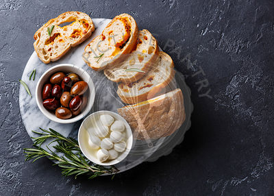 Olives, mini Mozzarella cheese and sliced Ciabatta bread with cheese on dark background copy space
