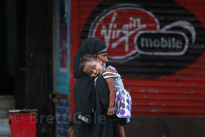 A woman carries her daughter on a street near Crawford Market, Mumbai, India.