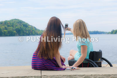 Two young women enjoying a sunny afternoon in a riverside park
