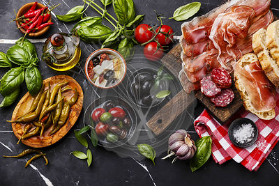 Italian snacks food with Ham, Sliced bread Ciabatta, Olives, Feta cheese with dried tomatoes, Garlic, Sausage and Pepperoni pepper on dark marble background