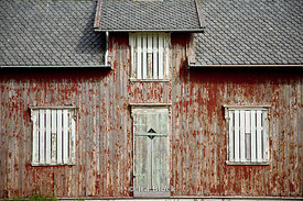 A weathered, once red, home on the island of Vaeroya in Norway.