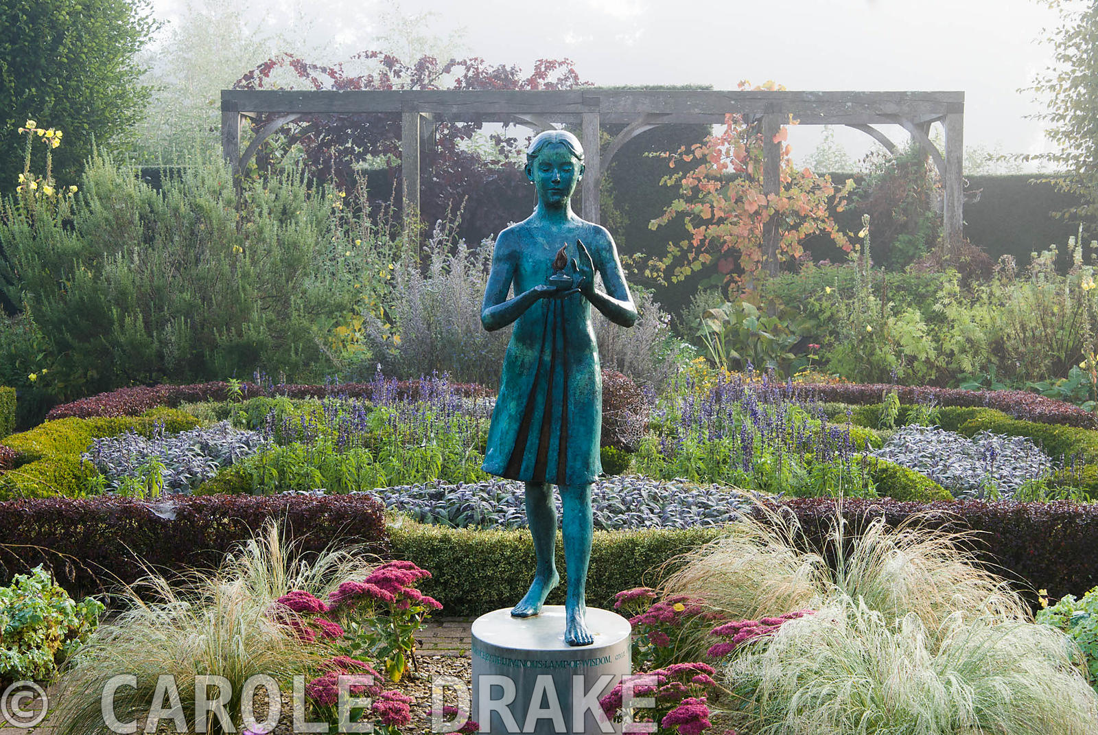 The Formal Garden, with knot garden made of box and berberis, contains a statue of a girl holding the lamp of wisdom by Natha...