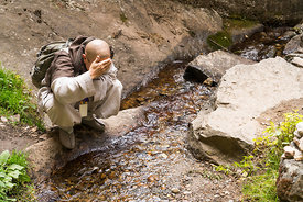 A monk washing his face near Paro Taktsang in upper Paro valley, Bhutan.