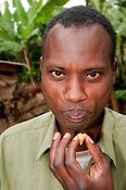 Man tasting honey which will be used in the home and sell also. Rwanda.